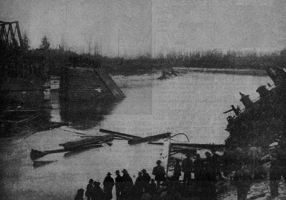 A grainy, black and white newspaper photograph showing the Skagit River strewn with debris.  In the corner of the photograph, a steam locomotive is half submerged in the river. A crowd of people is gathered, watching the scene.